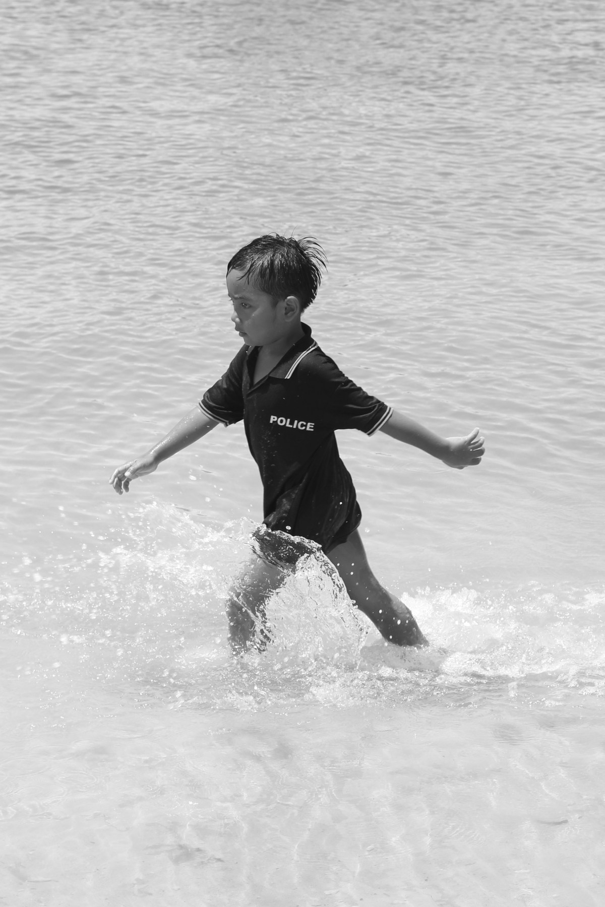 Child policeman walking into the water